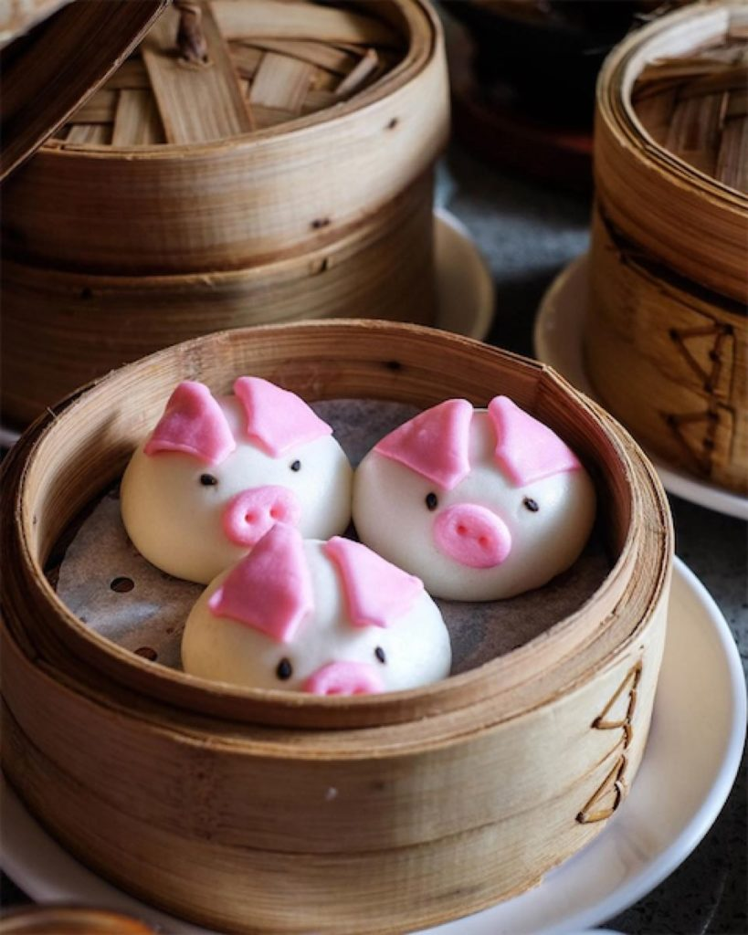 3 pig-shaped char siew baos on a steamer basket