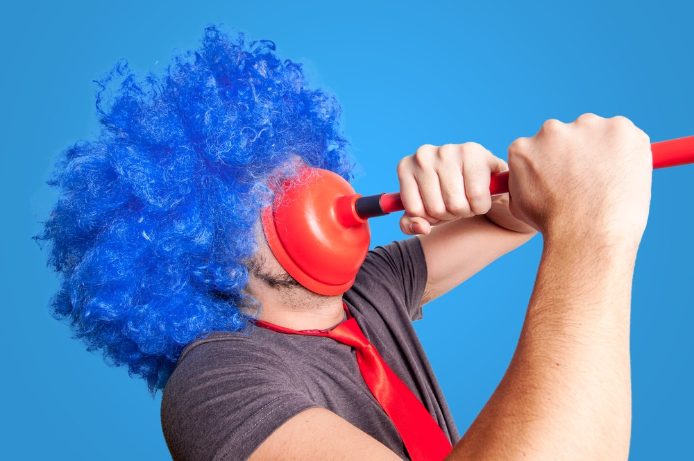 Male with a blue clown wig trying to remove a red plunger stuck to his face