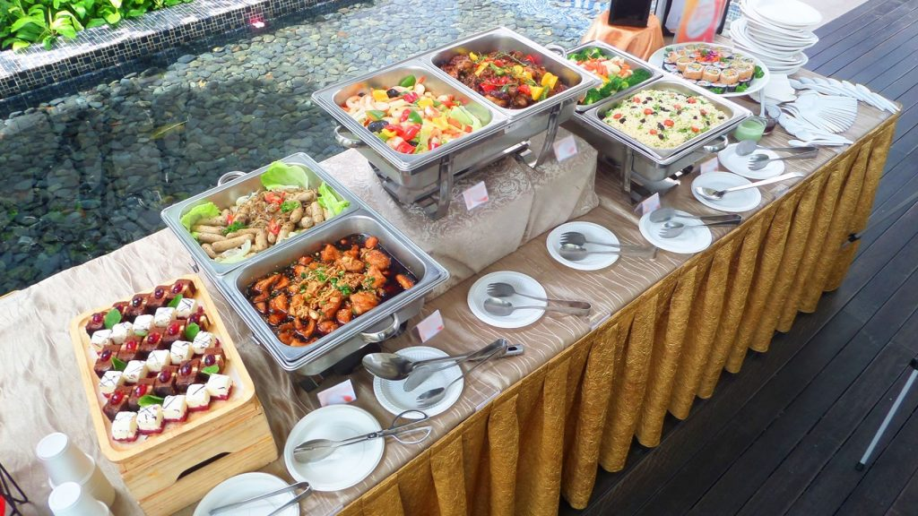 Buffet catering trays filled with food beside a pond in Singapore