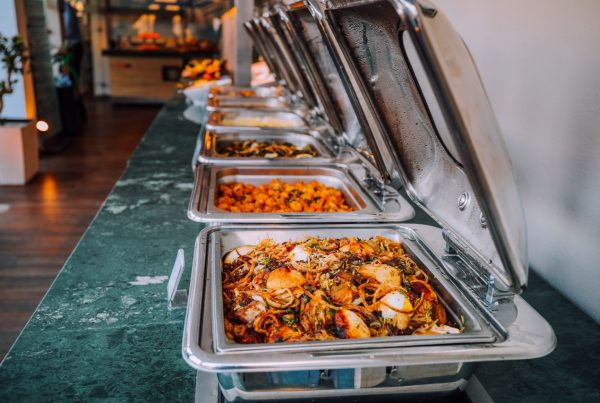 Buffet catering trays with food on a green table