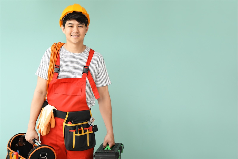 An electrician with tools and work attire