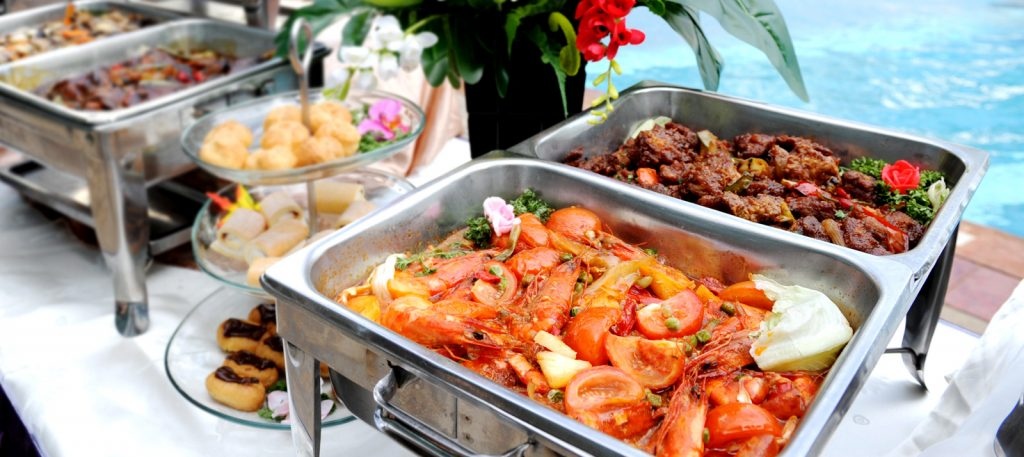 Trays of buffet catering food overlooking a swimming pool in Singapore