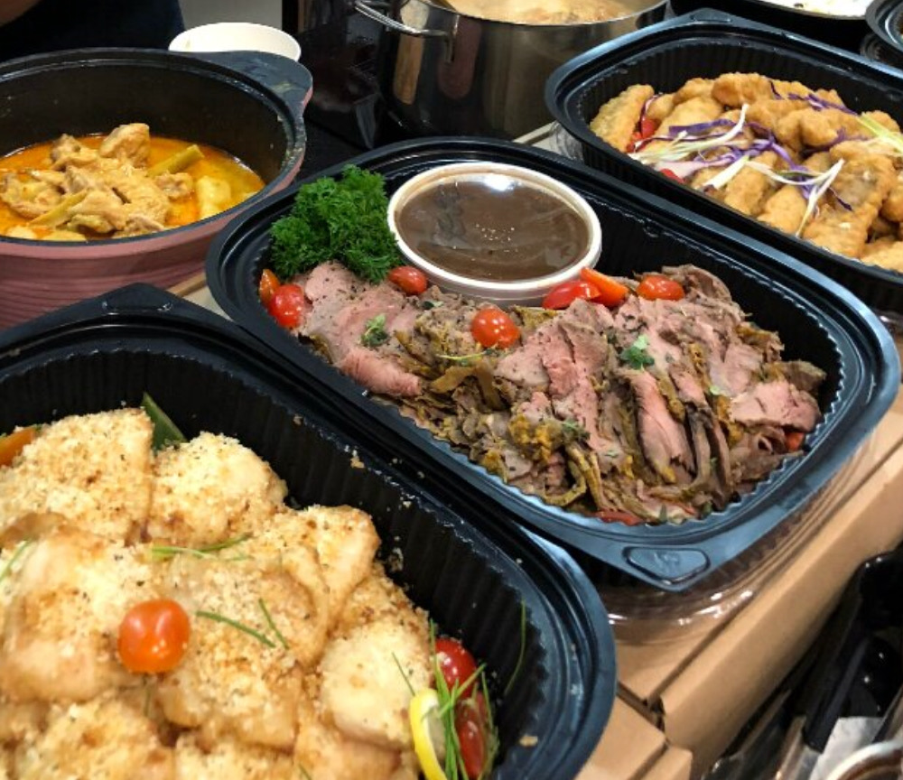 An assortment of buffet catering items in black trays in Singapore