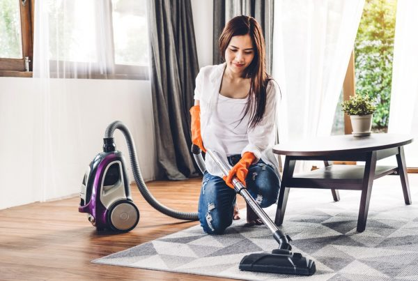 A woman wearing gloves and vacuuming a carpet at home