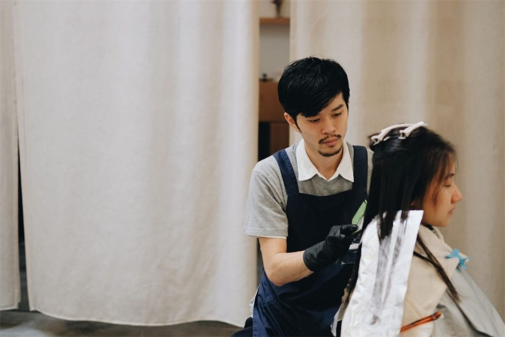 A male Japanese stylist dyeing the hair of a woman
