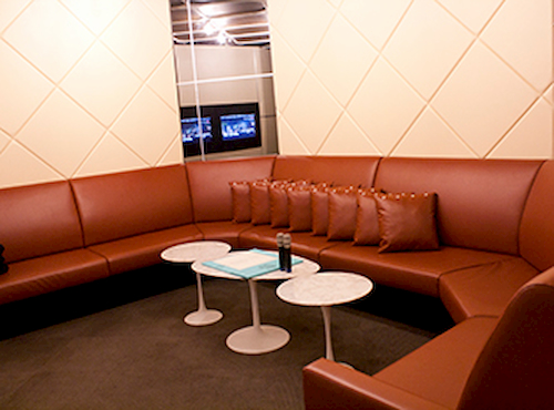 Ksuites ktv room with brown leather sofa and white tables