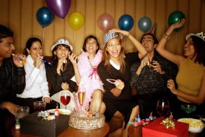 A group of people having a party, with balloons, a cake, presents, and party poppers on the table