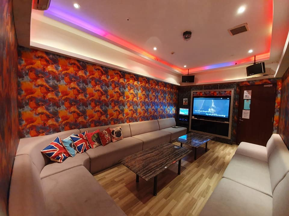 Ten dollar ktv club room with beige sofa, a brown table, colorful lights and tv