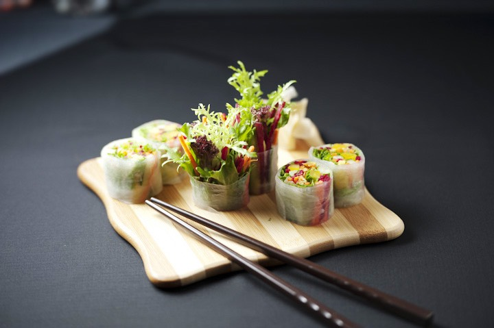 vegetable wraps on a wooden board and a pair of chopsticks