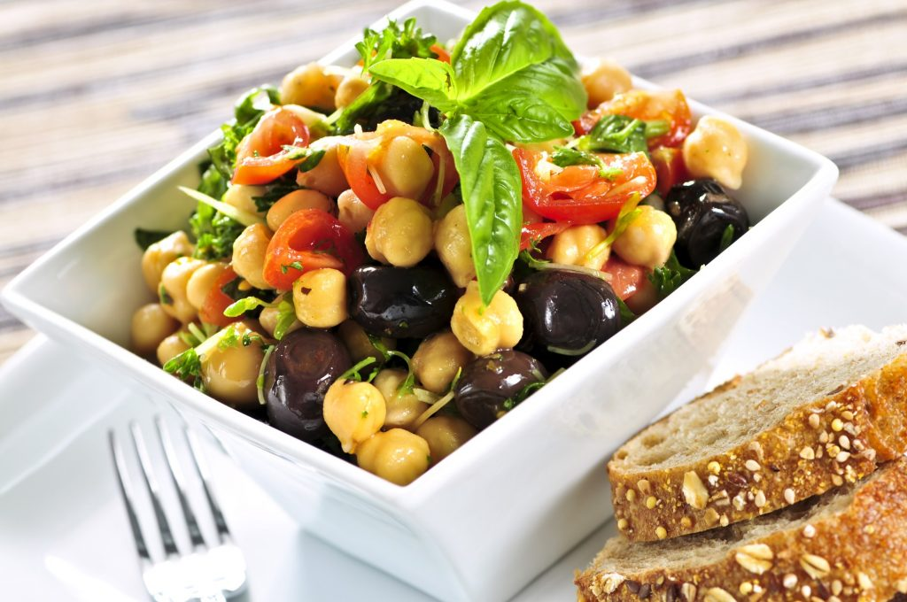 A bowl of chickpea salad with toast on the side