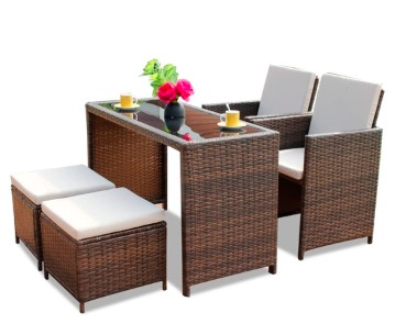 Wicker table, 2 wicker chairs, and 2 wicker stools, with cushions on top of the chairs and stools