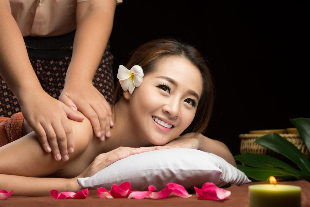 A woman smiling as someone is massaging her