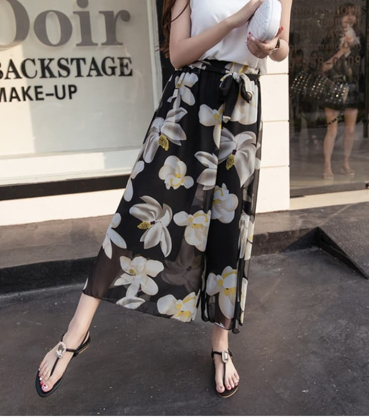 A woman wearing a black and white floral chiffon culottes