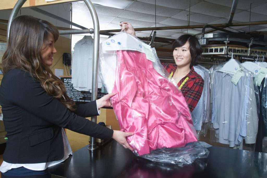A woman giving a dry cleaned dress to another woman