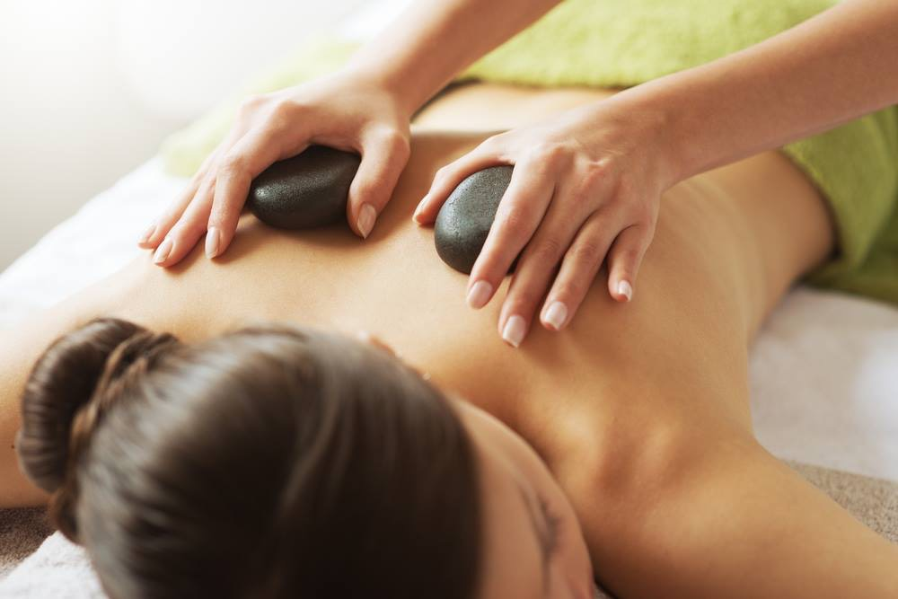 A woman getting massaged with hot stones
