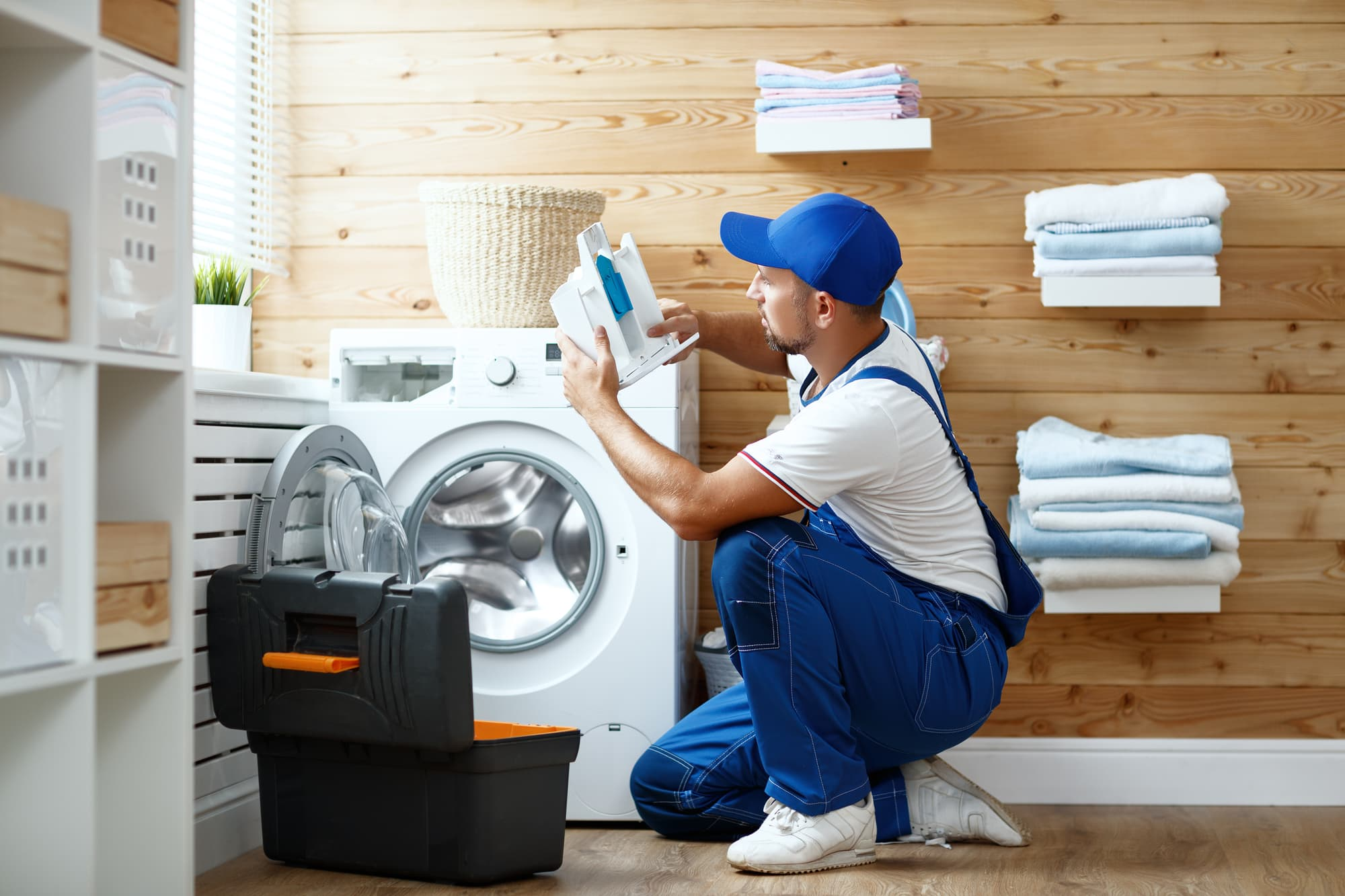 washing machine and a repair man in laundry area