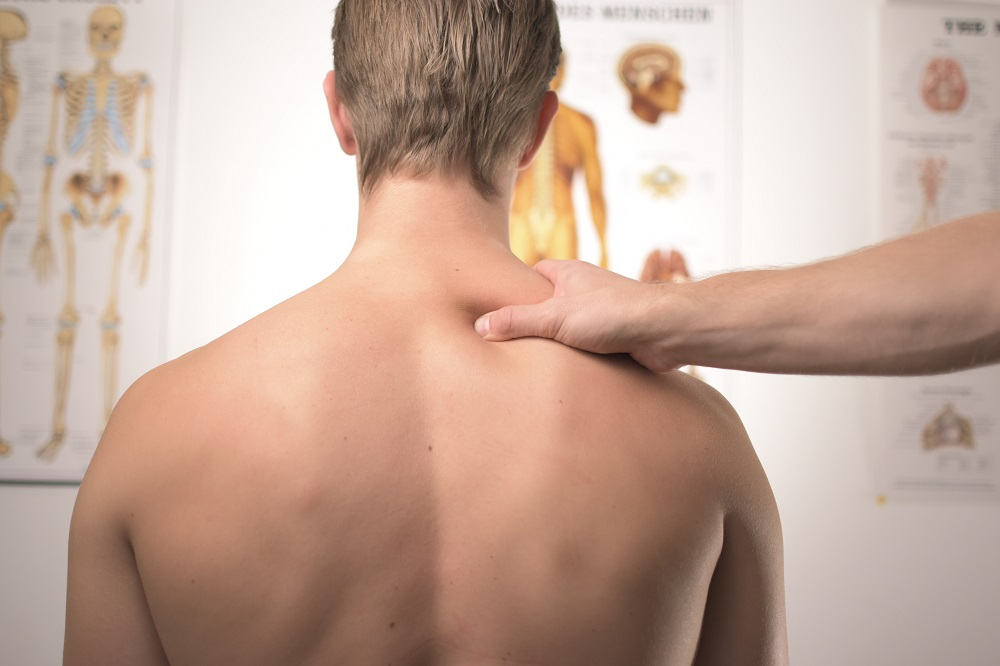 chiropractor pressing the upper back part of a man