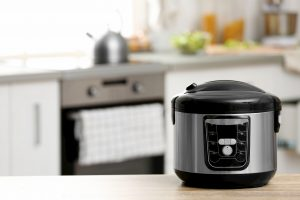 Modern electric rice cooker on table in kitchen