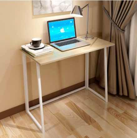 a foldable computer desk with computer and other items in a room