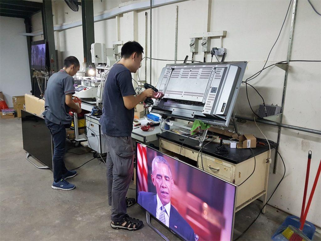 Technicians from TVGuru repairing a TV