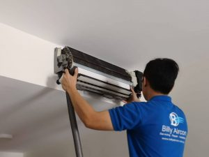 A technician from Billy Aircon servicing an aircon unit
